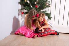 Två lilla systrar som använder minnestavlaPC:n Royaltyfria Foton