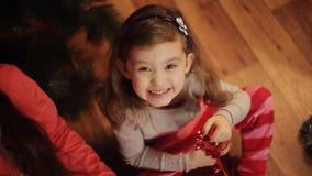 Två lilla systrar som dekorerar julgranen med gran-kotten nytt förberedelseår för 2008 ingredienser Lyckliga flickor och familj stock video