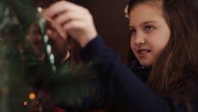 Två lilla systrar som dekorerar julgranen med gran-kotten nytt förberedelseår för 2008 ingredienser Lyckliga flickor och familj arkivfilmer
