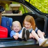 Två lilla systrar som går till en bilsemester Royaltyfria Foton