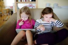 Två lilla systrar som har gyckel, medan genom att använda den digitala minnestavlan Royaltyfri Bild