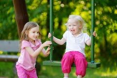 Två lilla systrar som har gyckel på en gunga Royaltyfria Bilder