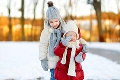 Två lilla systrar som har gyckel på snöig vinterdag arkivbilder
