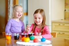 Två lilla systrar som målar färgrika påskägg Arkivfoton