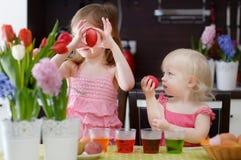 Två lilla systrar som målar påskägg Fotografering för Bildbyråer