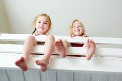 Två lilla systrar som omkring bedrar, spelar och har gyckel i tvilling- britssäng Arkivbilder