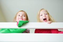 Två lilla systrar som omkring bedrar, spelar och har gyckel i tvilling- britssäng Royaltyfria Bilder