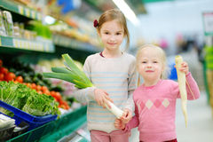 Två lilla systrar som shoppar i ett matlager arkivfoto