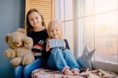 Två lilla systrar som sitter nära fönster med gåvor royaltyfri fotografi
