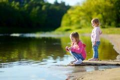 Två lilla systrar som spelar vid en flod royaltyfri bild