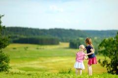 Två lilla systrar som tycker om en härlig sikt Arkivbild