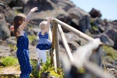 Två lilla systrar som tycker om en sikt på havet Arkivfoto