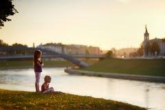 Två lilla systrar som tycker om en sikt på solnedgången Arkivbilder