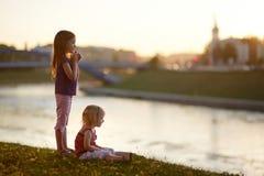 Två lilla systrar som tycker om en sikt på solnedgången Arkivfoto