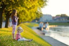 Två lilla systrar som tycker om en sikt på solnedgången Fotografering för Bildbyråer