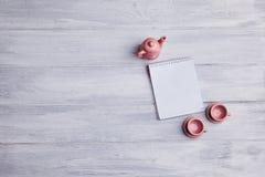 Två lilla tekoppar med en rosa kokkärl och en anteckningsbok på en träbakgrund royaltyfri foto