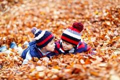 Två lilla tvilling- pojkar som ligger i höstsidor i färgrika kläder Lyckliga syskonungar som har gyckel i höstskog eller arkivbilder