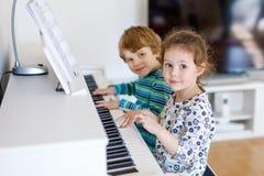 Två lilla ungar flicka och pojke som spelar pianot i vardagsrum eller musikskola Arkivbild
