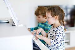 Två lilla ungar flicka och pojke som spelar pianot i vardagsrum eller musikskola Royaltyfria Bilder
