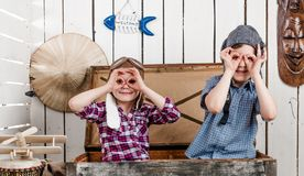 Två lilla ungar i pilot- hattar som gör exponeringsglas med händer fotografering för bildbyråer