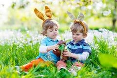 Två lilla ungar som spelar med påskchoklad royaltyfri fotografi