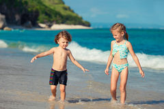 Två lilla ungar som spelar på stranden arkivbild