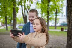 Två lilla ungar som tar utomhus- selfie Begrepp för förälskelsekamratskapgyckel Små vuxna människor royaltyfria foton