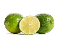 Två limefrukter med halva av en saftig limefrukt arkivfoto