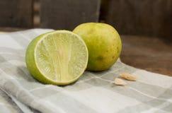 Två limefrukter och kasju på näsduken Arkivfoto