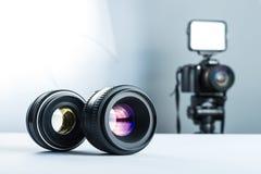 Två linser på en vit tabell i stuidio, mot bakgrunden av DSLR-kameran som ska tändas, och softbox royaltyfri bild