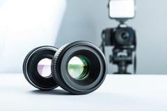 Två linser på en vit tabell mot bakgrunden av kameran som ska tändas, och softbox fotografering för bildbyråer