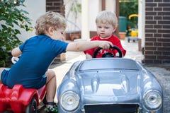 Två lite broderlitet barn som leker med bilar Arkivfoto