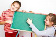 Lite schoolgirls med den tomma blackboarden Royaltyfria Bilder