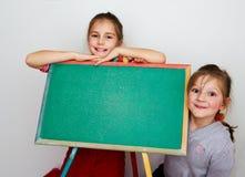 Lite schoolgirls med den tomma blackboarden Fotografering för Bildbyråer