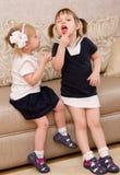 Två liten flicka äter godisar Arkivfoton
