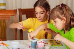 Två liten flicka (systrar) som målar på påskägg Arkivfoto