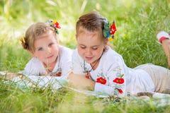 Två liten flickaläseböcker på den gröna ängen royaltyfri bild