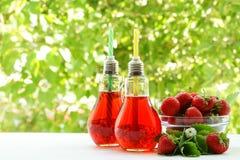 Två ljusa kulor med jordgubbefruktsaft och jordgubbar i en bunke Royaltyfria Foton