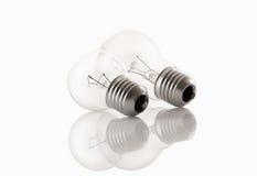 Två ljusa kulor på vit med reflekterar Fotografering för Bildbyråer