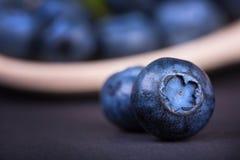 Två ljusa röda blåbär på en svart bakgrund, närbild Sommarbär Hela och nya blåbär arkivfoton