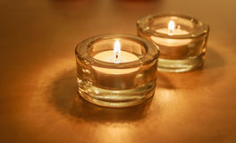 Två ljusa stearinljus för te i exponeringsglas på guld Fotografering för Bildbyråer