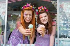 Två ljust rödbrun haired damer som rymmer glass från lastbilen arkivfoto
