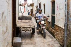 Två lokala män som kör en motorcykel till och med smala gator av stenstaden, gammal kolonial mitt av den Zanzibar staden, Unguja, royaltyfri bild