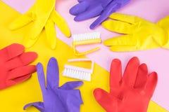 två lokalvårdborstar som omges av en uppsättning av mång--färgade handskar för att skydda dina händer, från skada vid kemiska ren arkivbilder