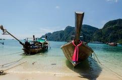 Två longtailfartyg på en strand Arkivfoton