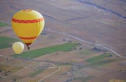 Två luftballonger som flyger över landet arkivfoto