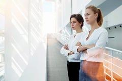 Två lyckade kvinnliga entreprenörer med korsade armar som ser in i fönstret, medan stå i modern kontorsinre, arkivfoto