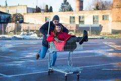 Två lycklig man och kvinna som har gyckel på shoppingvagnen utomhus arkivfoton