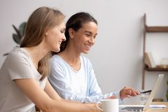 Två lyckliga affärskvinnor arbetar tillsammans för att samarbeta på bärbara datorn i regeringsställning arkivfoton