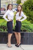 Två lyckliga affärskvinnor i den vita skjortan Fotografering för Bildbyråer